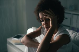 Sad depressed woman suffering from insomnia, she is sitting in bed and touching her forehead, sleep disorder and stress concept - stock photo