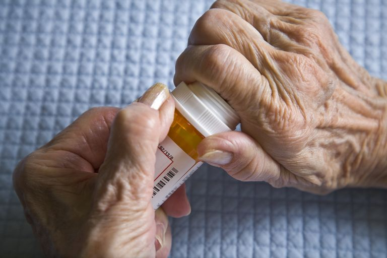 arthritis hands trying to open prescription medicine pill bottle