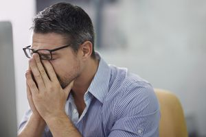 A stressed man sitting at computer rubbing his face