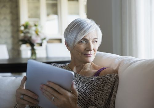 older woman looking at tablet on couch and smiling