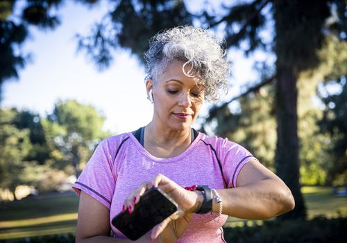 An older Black woman exercising outside, she has stopped to look at her fitness tracker.