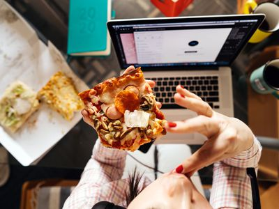 A middle-aged woman eating while sitting at a computer