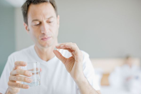 man with glass of water and white pill