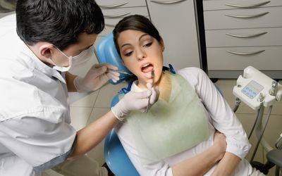 Dentist examining a woman's teeth.