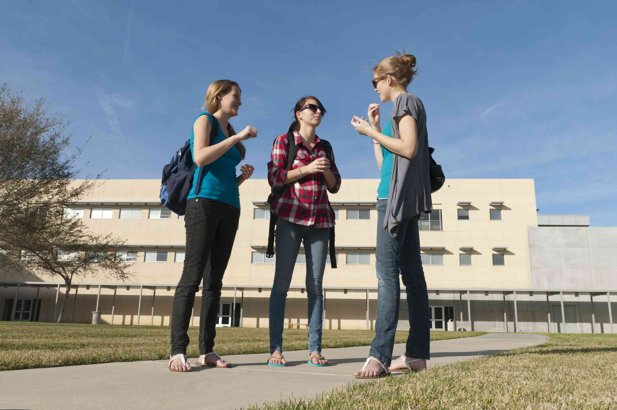 Three college-aged women having a conversation in ASL outside school
