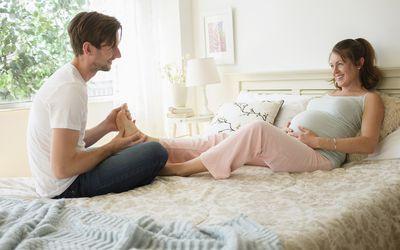 Man massaging pregnant womans feet