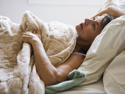 Woman lying in bed staring at ceiling
