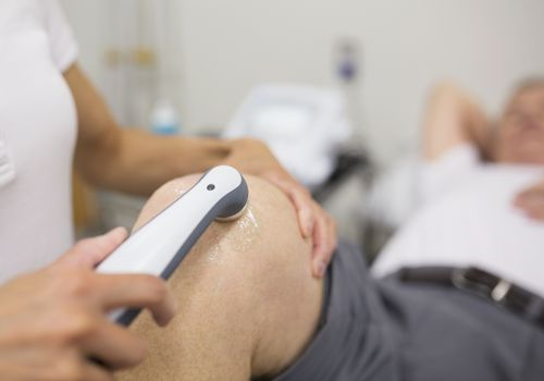 A physical therapist performs a therapeutic ultrasound on a patient's knee.