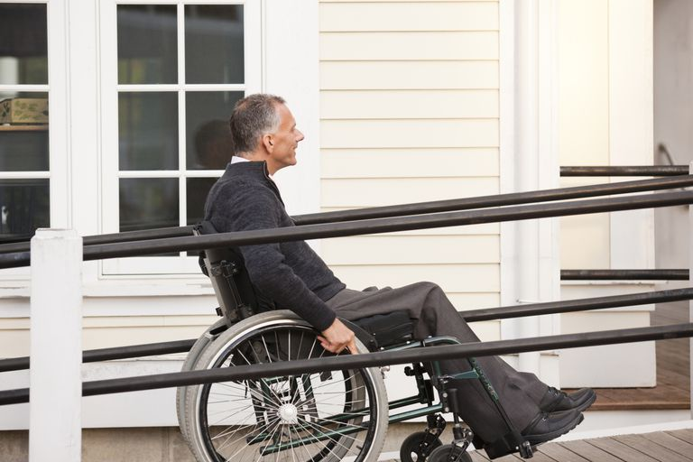 man going up wheelchair ramp