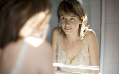 a woman looking into the mirror