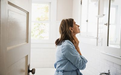 Woman looking in bathroom mirror, touching neck - stock photo