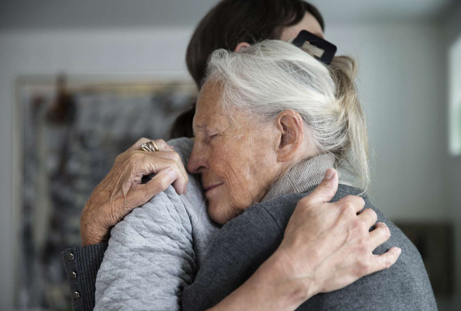 Older mother with dementia and daughter hugging