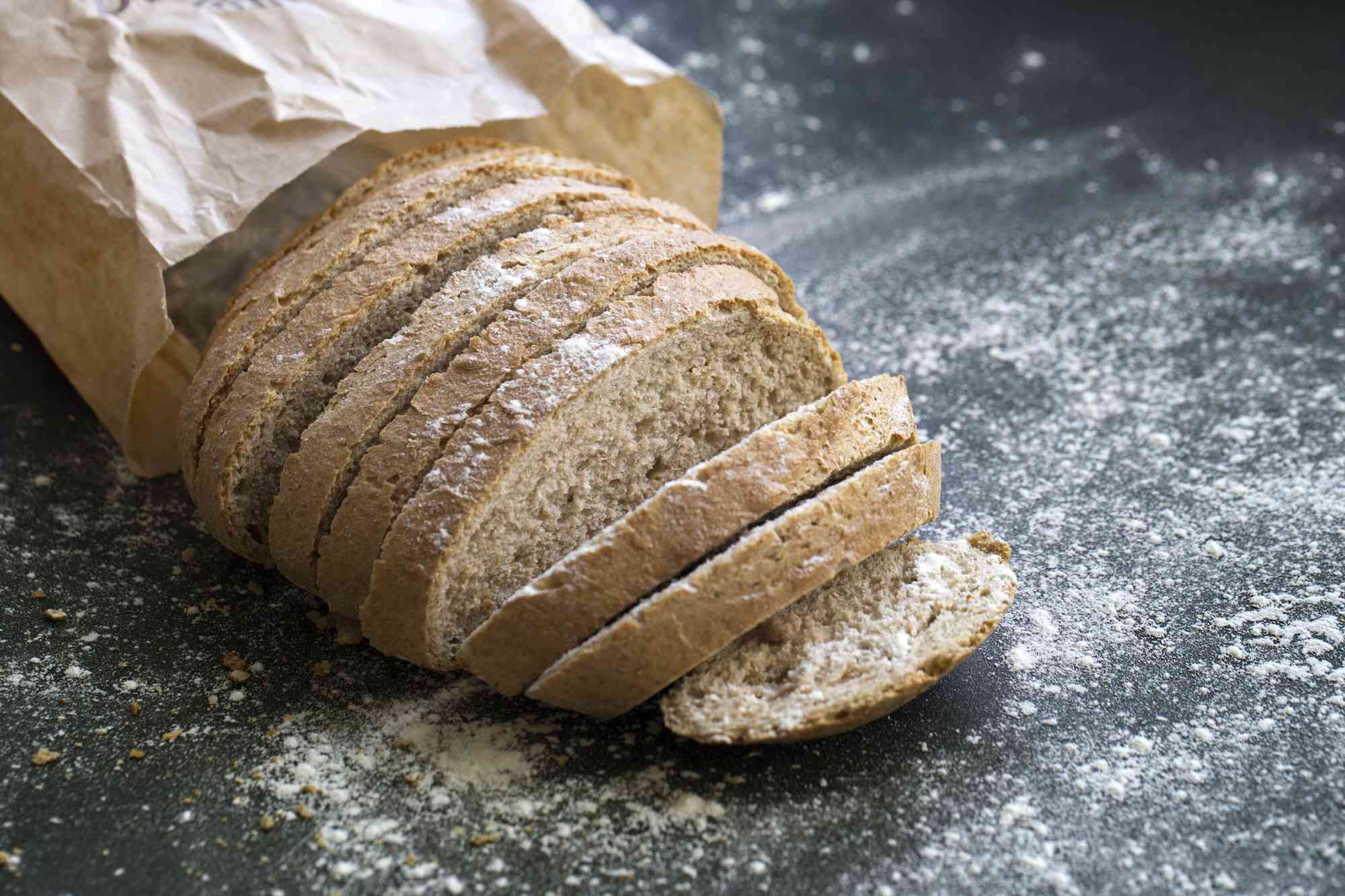Wheat bread on a table surrounded by flour