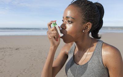 Woman using inhaler at the beach