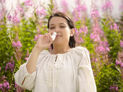 Woman using a nasal spray outside