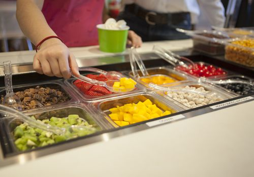 Woman scooping mango chunks from a toppings bar at a frozen yogurt place