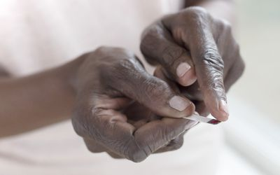 Close up of a Black person's hands pressing a finger to a blood stick test strip.