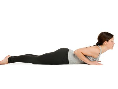 Full Length Of Young Woman Doing Yoga Against White Background