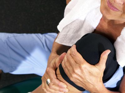 Mature woman in gym holding painful knee