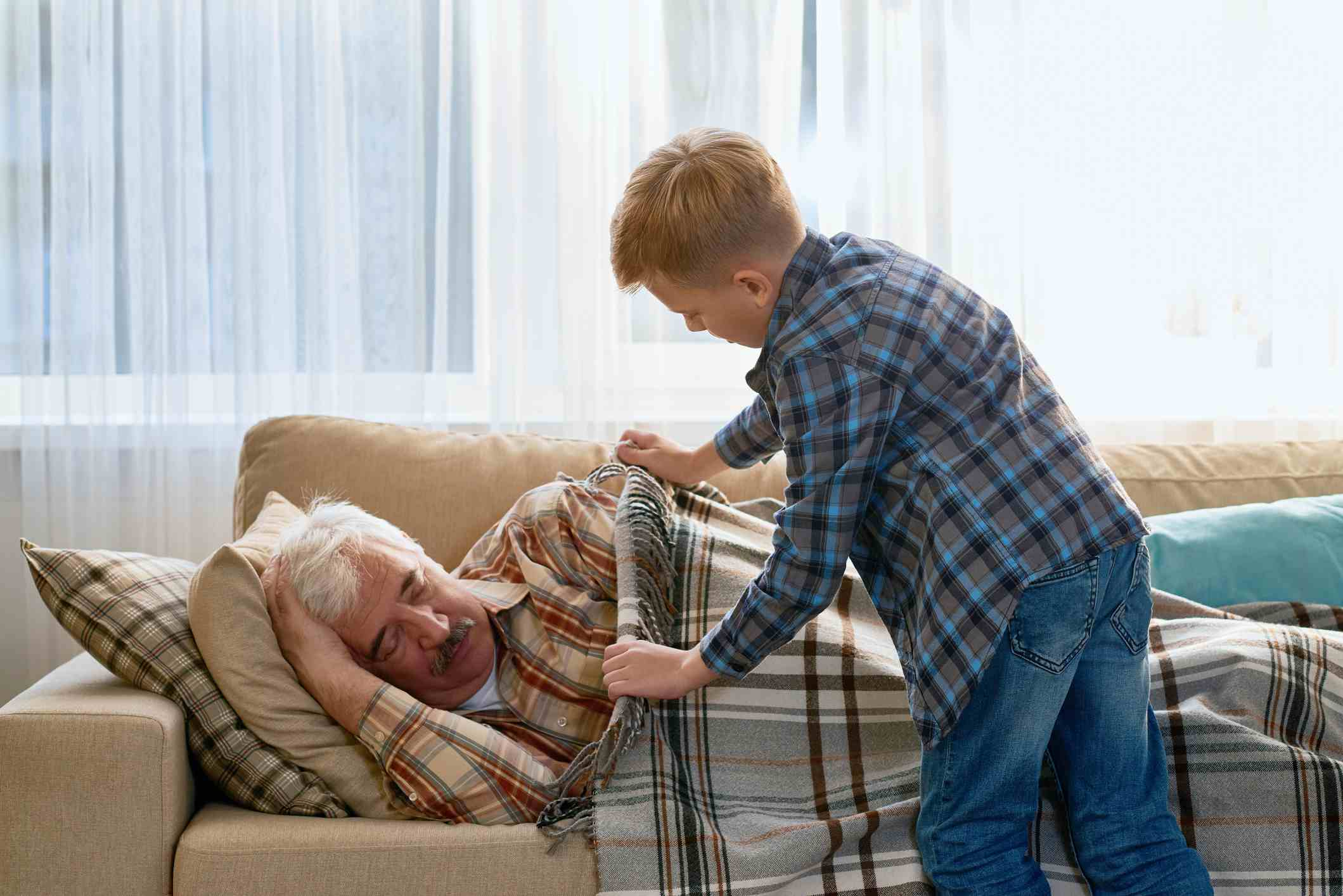 Careful grandson covering grandpa with blanket