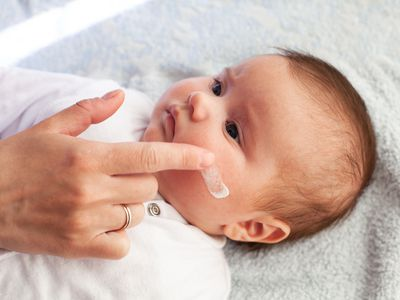 An adult wipes cream on a light skinned baby's face