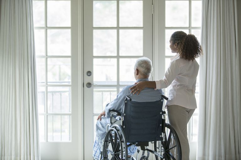 elderly man in wheelchair next to young woman