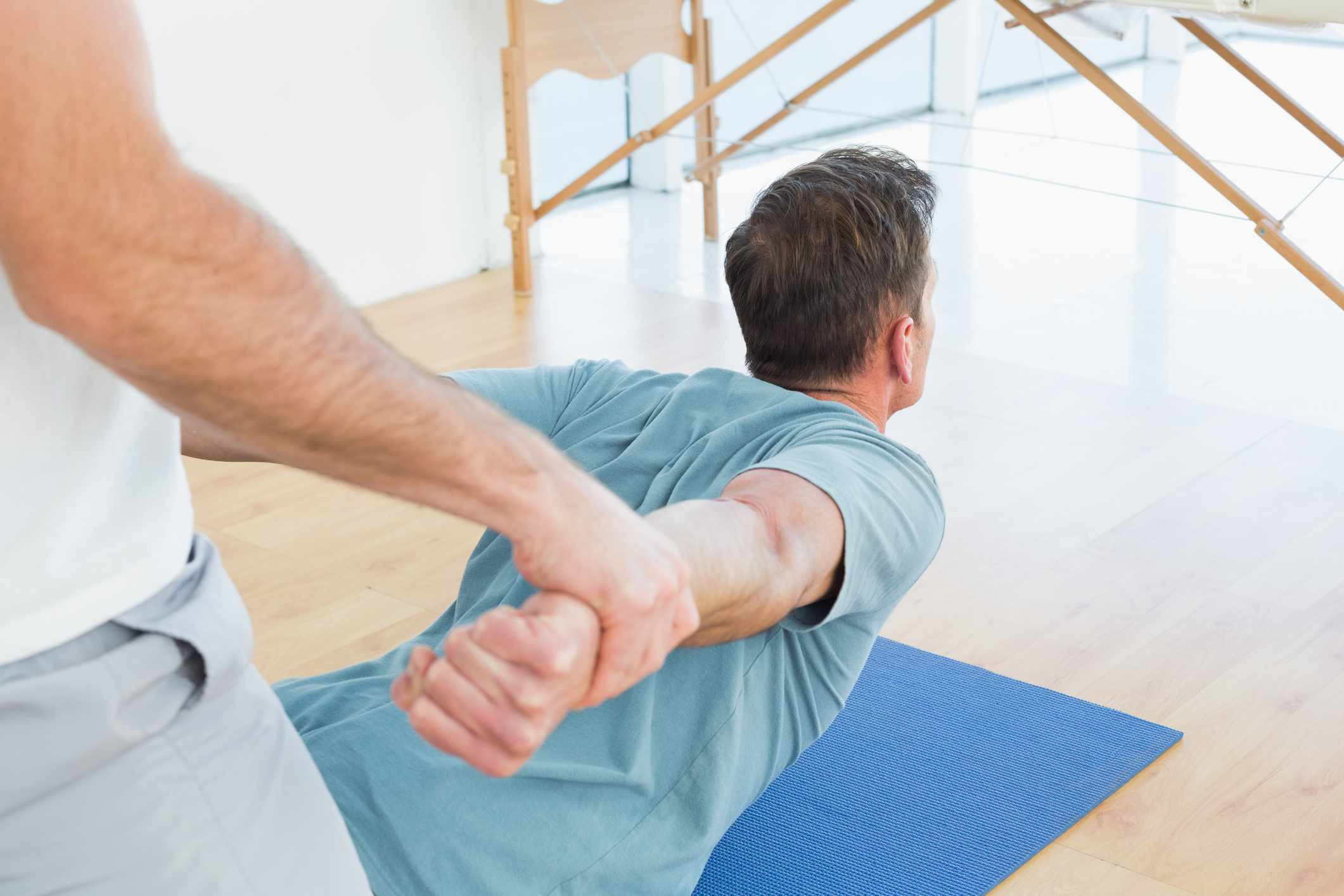 A therapist assisting a man with stretching exercises