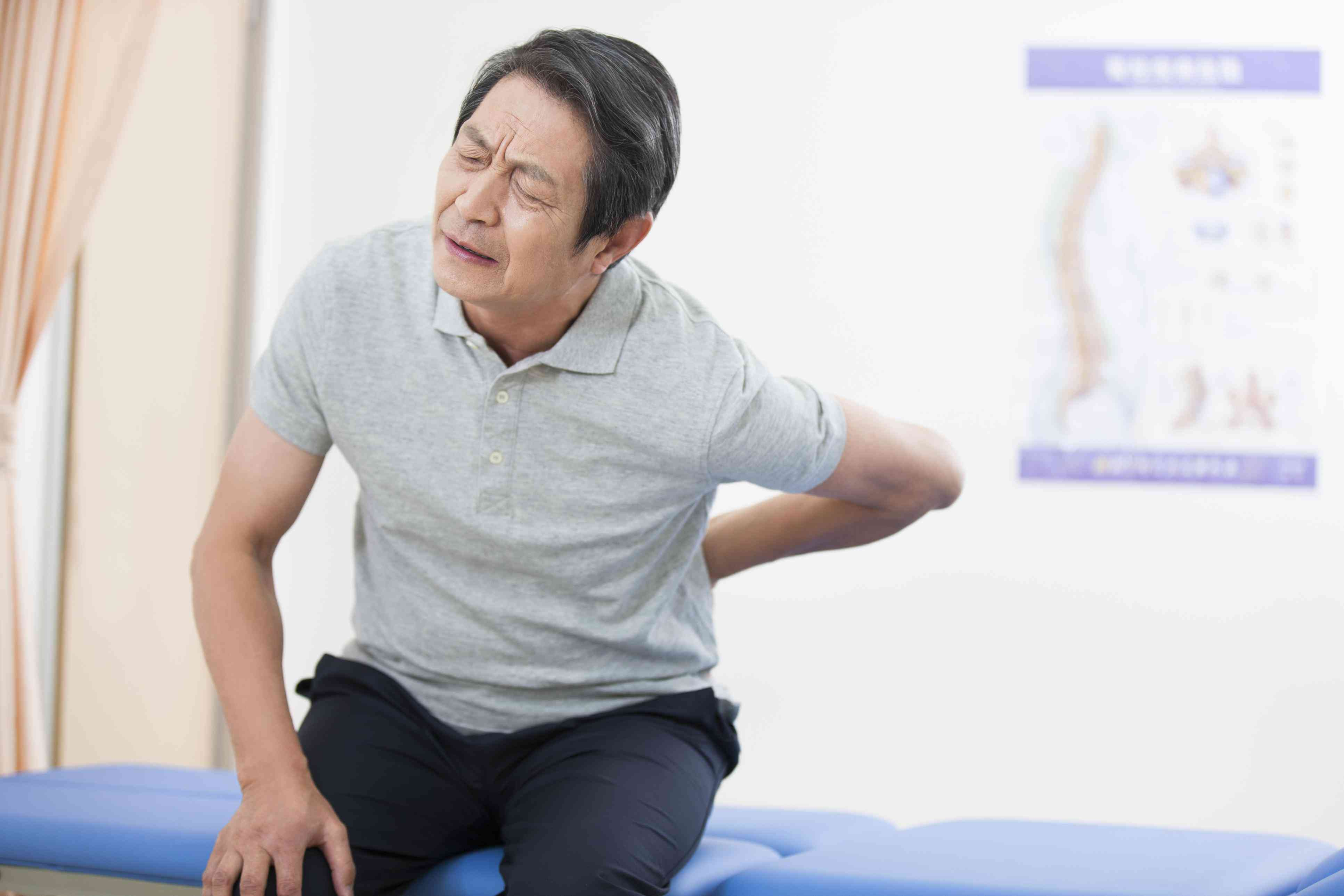 Man in pain holding his back