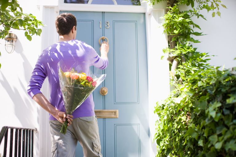 Man with bouquet knocking on a front door