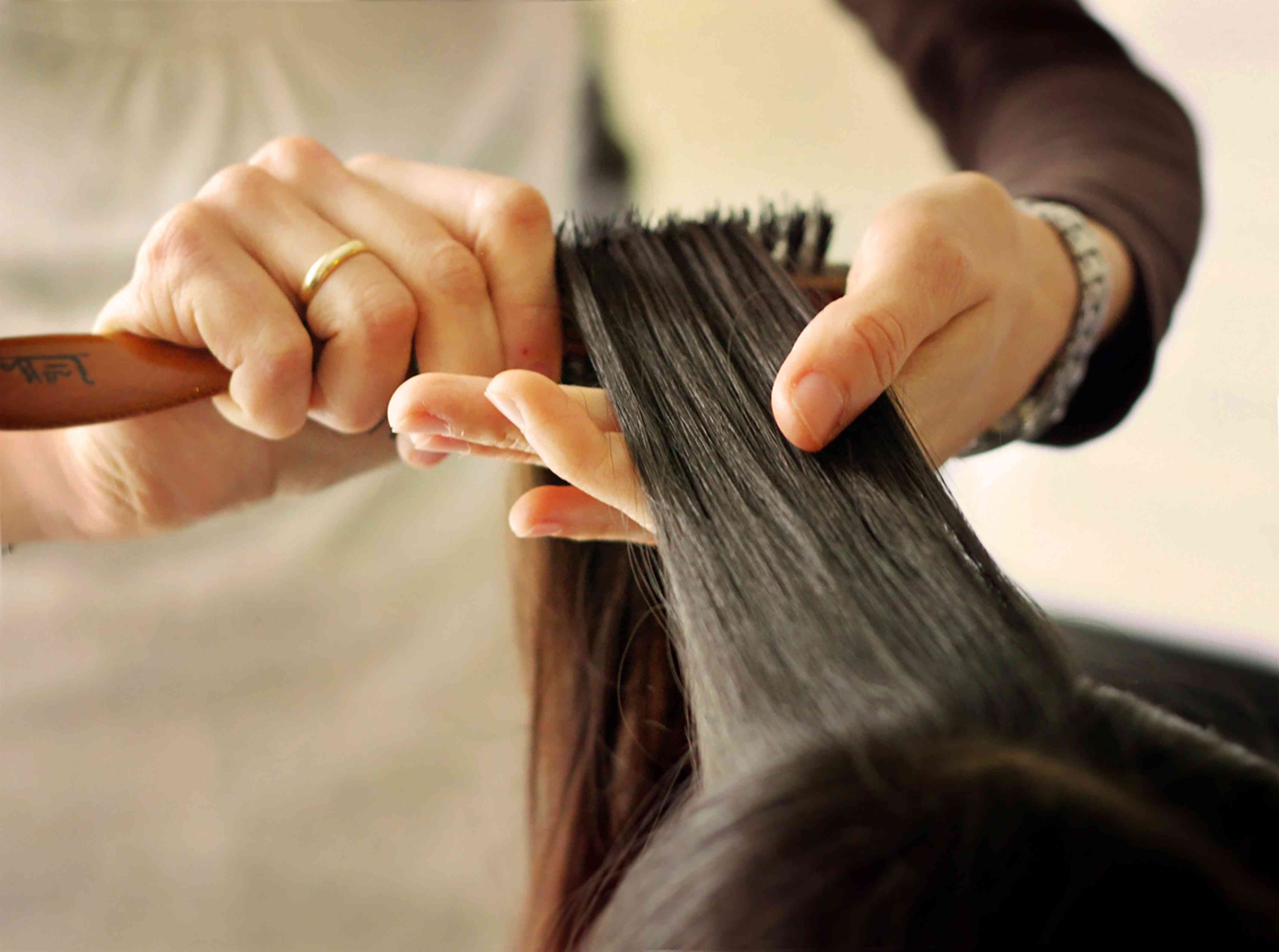 A woman getting castor oil combed into her hair