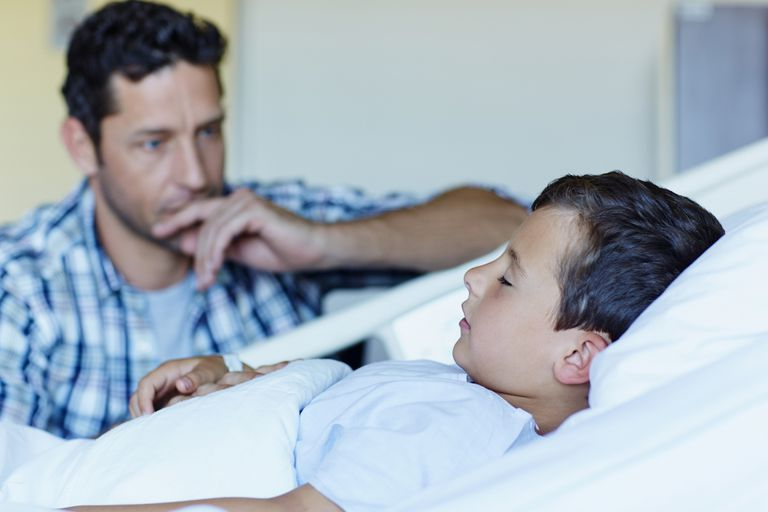 father with ill son sleeping in hospital