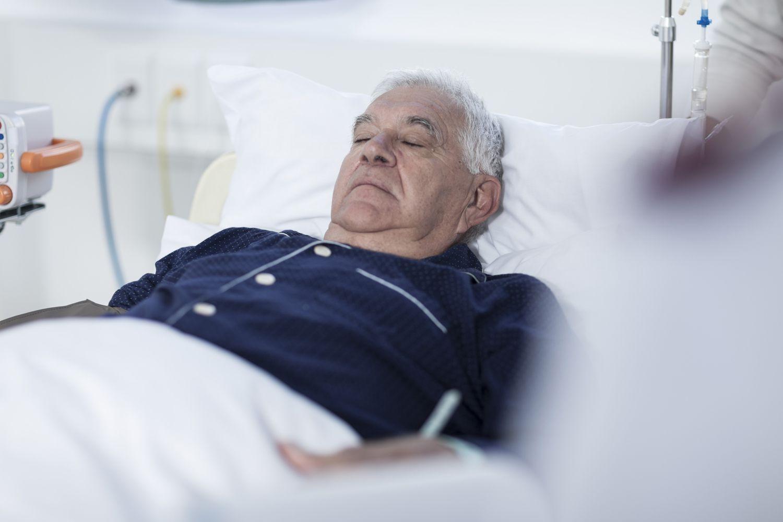 An elderly man in a hospital bed.
