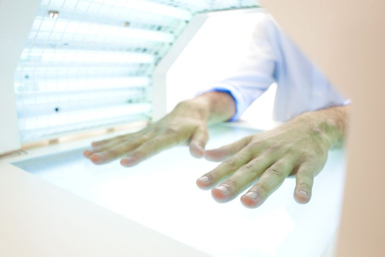 Man with hands in a light box
