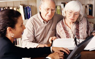 patient advocate showing computer to older couple