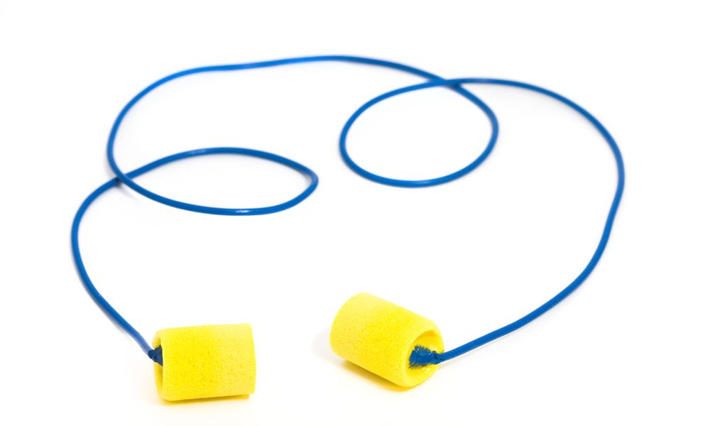 Yellow sponge ear plugs with blue wire, uncoiled on white background