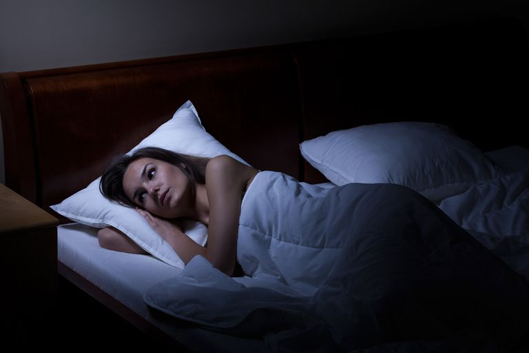 A woman in bed awake with insomnia wonders if it is a sign of pregnancy