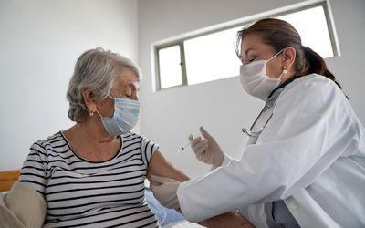 Older hispanic woman receiving a vaccine from a nurse.