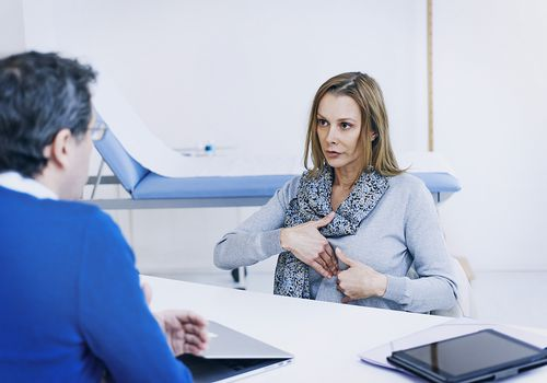 woman talking to doctor about stomach pain