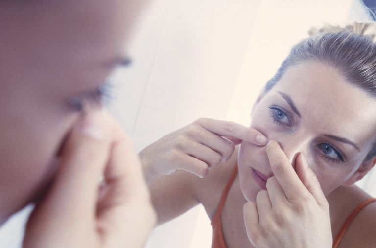 Woman popping pimple in a mirror