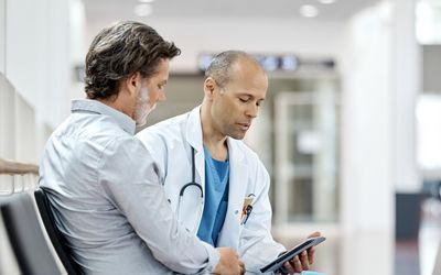 Male Doctor Counseling Mature Patient At Hospital