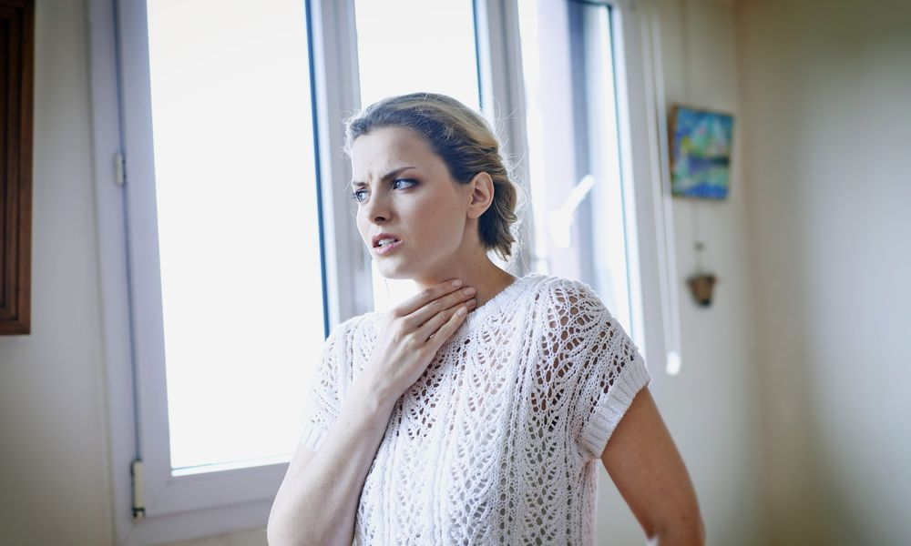 Woman suffering from a sore throat.