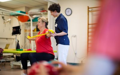 Therapist assisting senior woman in strengthening arms with resistance band