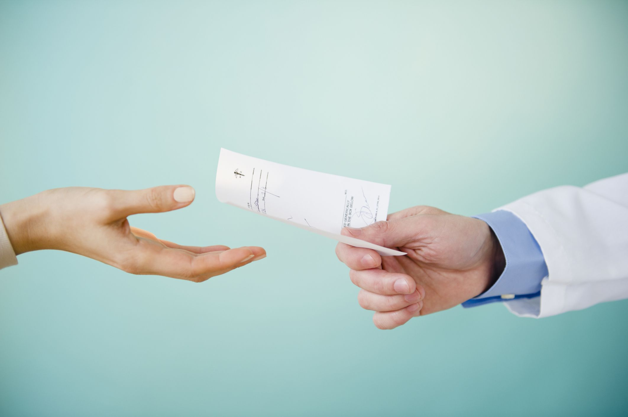 Prescription being handed to a patient by doctor - hands and paper only in shot