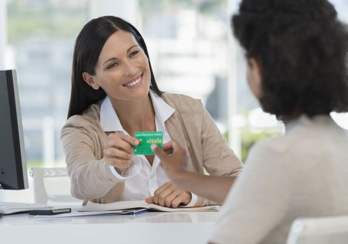 Receptionist giving card to a woman