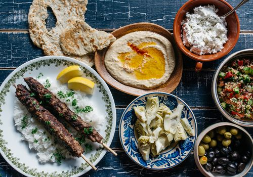 Plates and dishes with olives, artichoke hearts, hummus, and more