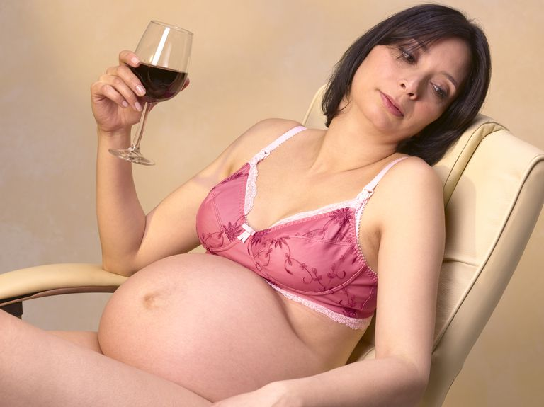 Pregnant woman holding red wine glass