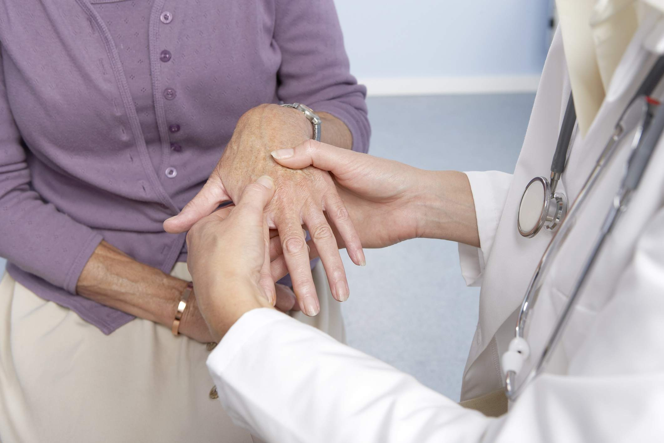 Photo of a doctor examining a woman's hand.