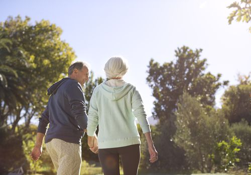 Senior couple holding hands and walking in park
