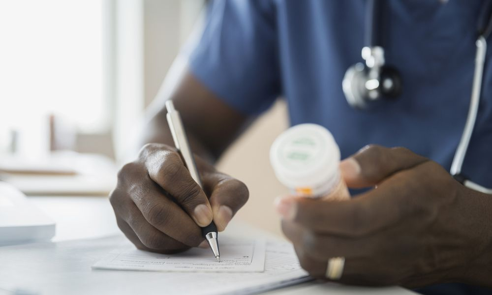 A doctor writes a prescription for medication.