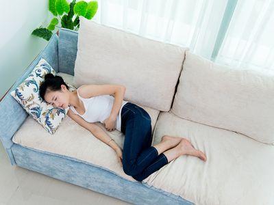 Young woman having stomachache on sofa.